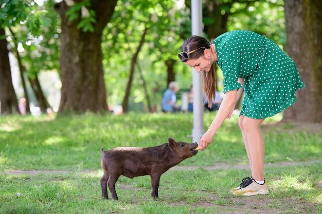 Девочка кормит поросёнка. на зеленом лугу. концепция устойчивости, любви к природе, уважения к миру и любви к животным. экологический, биологический, веганский, вегетарианский
