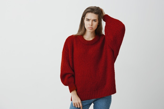 Girl feeling bothered not knowing answer to question. portrait of displeased gloomy european woman in trendy loose sweater, scratching back of head and frowning, confused and troubled over gray wall