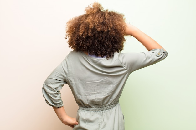 Girl feeling clueless and confused, thinking a solution, with hand on hip and other on head, rear view