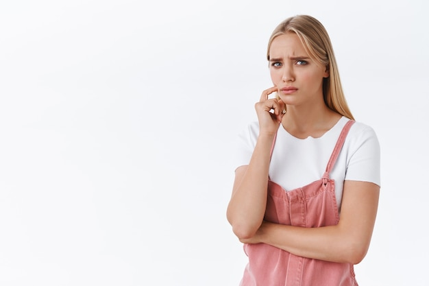Girl feeling concern and doubts, thinking about something troublesome and upsetting, frowning suspicious stare skeptical with disbelief touch face, having uneasy feeling, something worry her