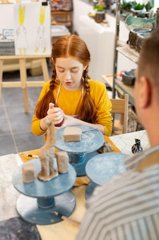 Girl feeling curious modeling animals with clay for the first time