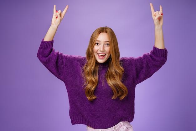 마침내 좋아하는 밴드 쇼의 티켓을 받고 흥분한 소녀는 로큰롤 제스처로 손을 들고 예라고 소리치고 활짝 웃고 행복하고 보라색 배경에 흥분했습니다. 복사 공간