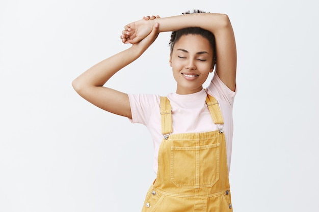 Girl feeling great after meditation. portrait of calm and relaxed feminine dark-skinned woman in stylish yellow dungarees, stretching raised hands with charming smile and closed eyes