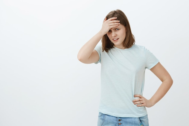 Girl feeling humiliated seeing mom near university. awkward displeased and embarrassed cute young woman in t-shirt covering face with palm on forehead looking from under forehead dissatisfied