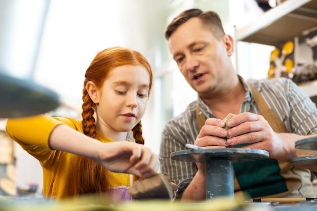 Девушка чувствует себя вовлеченной во время работы с глиной в художественной школе