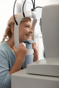Девушка чувствует себя радостной. красивая девочка-подросток чувствует себя радостной во время консультации офтальмолога