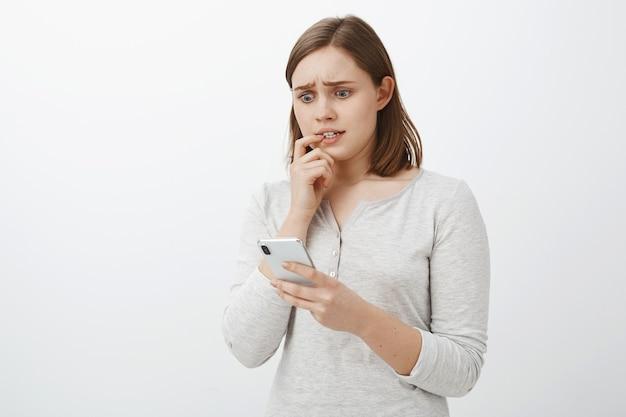 Девушка нервничает, отправляя деньги через приложение не тому человеку, кусая ноготь, хмурясь, с тревогой глядя на экран смартфона, потрясенная и напуганная плохими последствиями действий над серой стеной