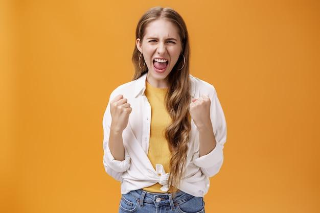 力を感じる少女は、元気を出して自信を高めるために叫ぶ問題を克服し、オレンジ色の背景に対してストレスを解放し、陽気で勝利のジェスチャーで上げられた握りこぶしを握り締めます。