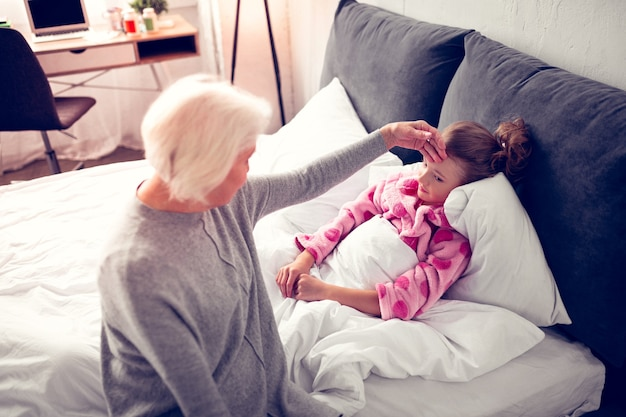 Girl feeling sick. caring grey-haired granny coming to her little girl lying in bed feeling sick