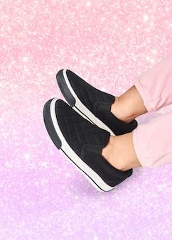 Piedi della ragazza in scarpa da tennis nera