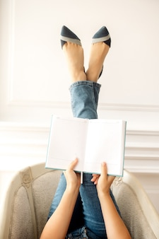 Girl feet in jeans and shoes with a diary