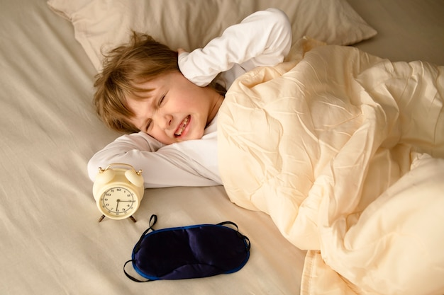 A girl a female child is naughty unhappy covered his ears with his hands when the alarm clock rings loudly in the morning refusing to get up early in the morning