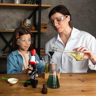 Ragazza e insegnante femminile che fanno esperimenti scientifici