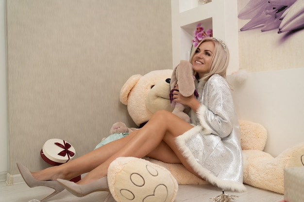 A girl in festive clothes hugs a soft toy presented to her and expresses joyful emotions