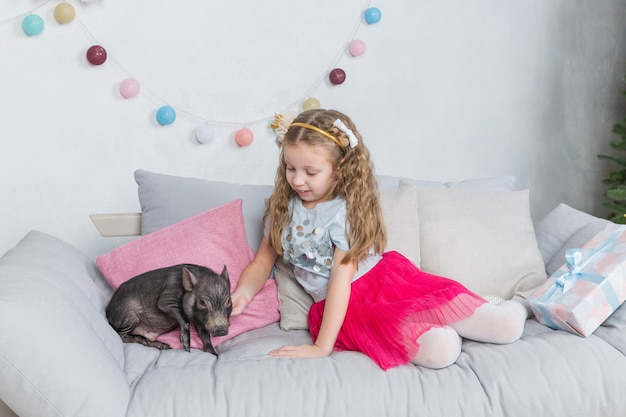 Girl in festive clothing and mini pig. pig symbol of 2019. black pig as symbil for 2019 in chinese horoscope. pet and child.friendship and care for the younger