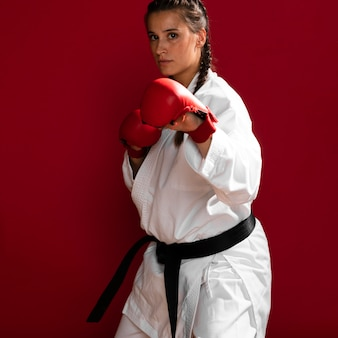 Girl fighter with box gloves on red background