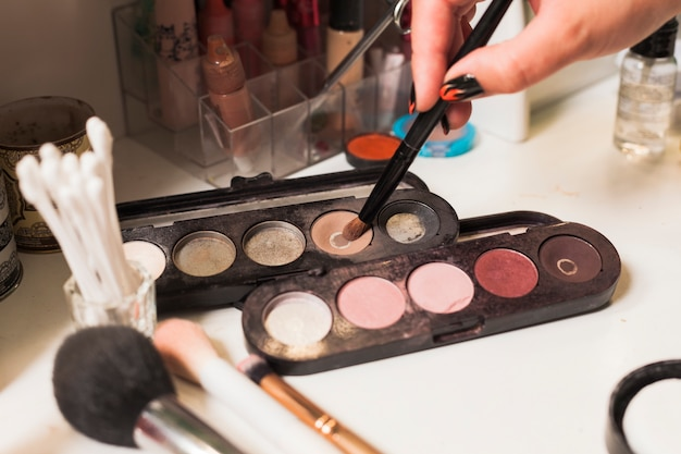 Girl filling brush with make up