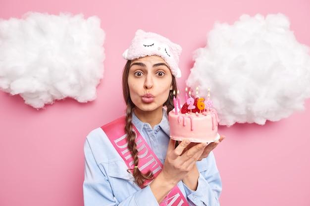 La ragazza ha finalmente il compleanno tiene le labbra piegate vuole baciare il fidanzato ringrazia per il regalo tiene una torta gustosa indossa una maschera per dormire e una maglietta accetta le congratulazioni