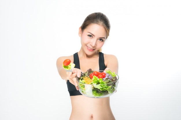 Girl in a fitness suite holds a salad bowl