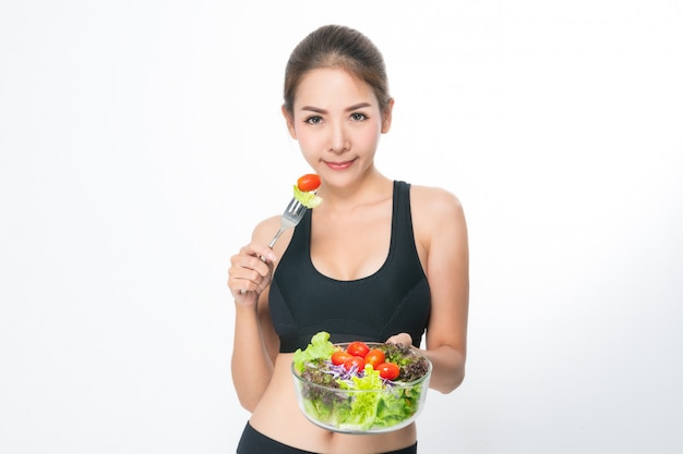 Girl in a fitness suite holds a salad bowl.