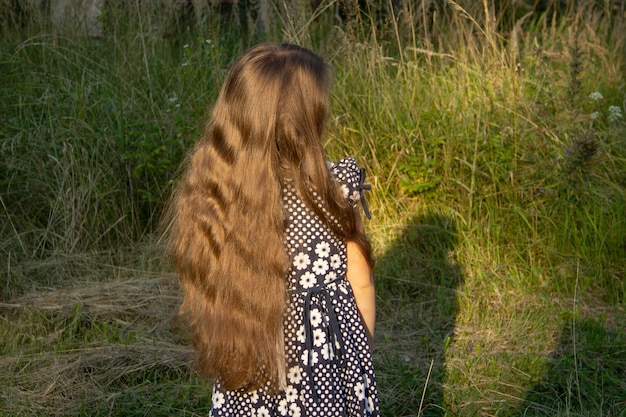 Girl, five, in dark dress stands back and shows off her long brown hair.