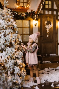 A girl of five or six years in winter pink clothes and ugg boots stands near the christmas tree