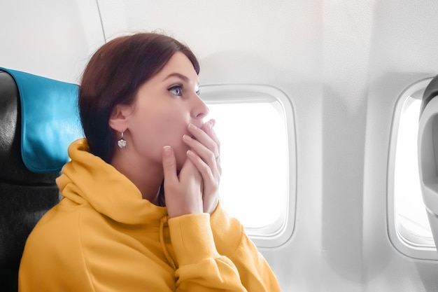 The girl flies on the plane, frightened closed his mouth with his hands, so as not to shout. concept by follow. flying by plane.