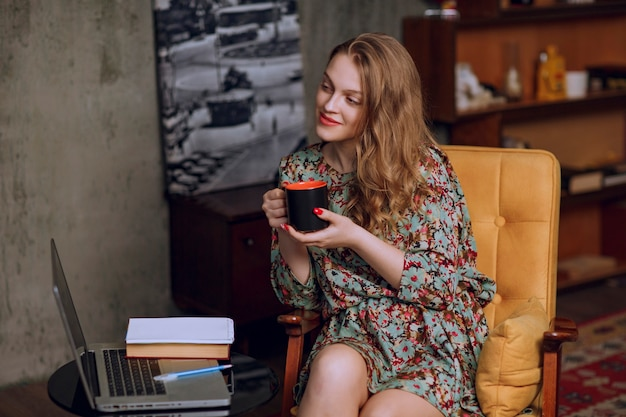 Girl in floral dress sitting and holding a brown coffee mug.