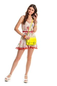 Girl in floral dress smiling. short summer dress with belt. lime bag and white sandals. cheerful model on white background.