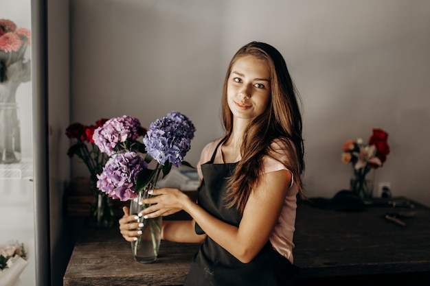 Girl florist in a black apron holds a vase with blue and lilac hydrangea .