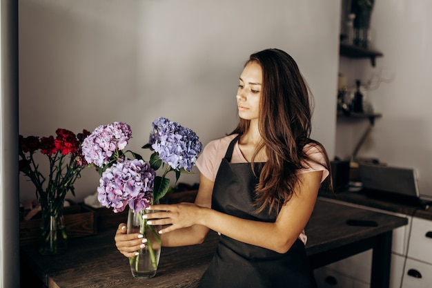 Girl florist in a black apron looks at vase with blue and lilac hydrangea .