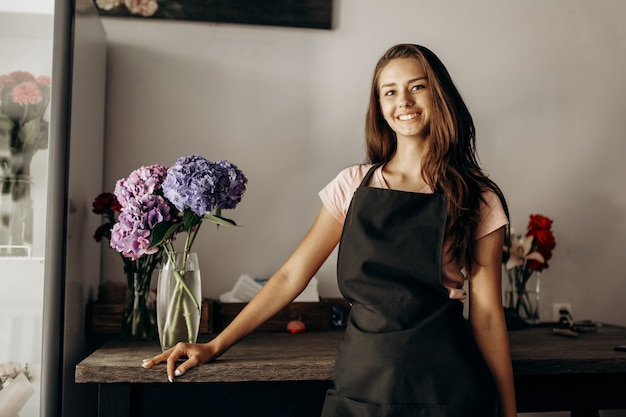 Girl florist in a black apron stands near the table with a vase with blue and lilac hydrangea .