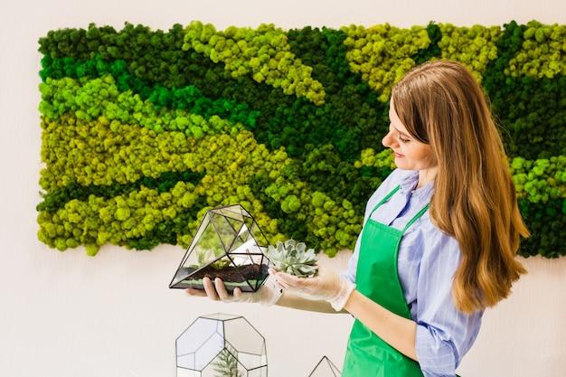 Girl florist garden plants in glass form, sand, succulents, gloves, moss, interior