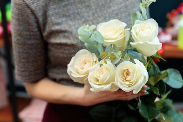 소녀 꽃집은 흰 장미 꽃다발을 보유하고 있습니다.