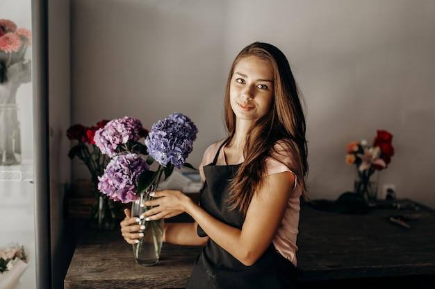 검은 앞치마를 입은 소녀 꽃집은 파란색과 라일락 수국이 있는 꽃병을 들고 있습니다.