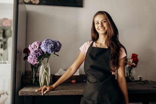 검은 앞치마를 입은 소녀 꽃집은 파란색과 라일락 수국이 있는 꽃병이 있는 테이블 근처에 서 있습니다.
