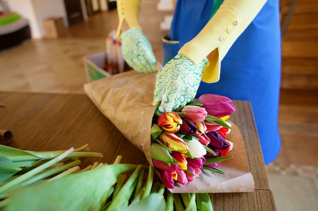 Girl florist is packing beautiful tulips in a flower shop in kraft paper