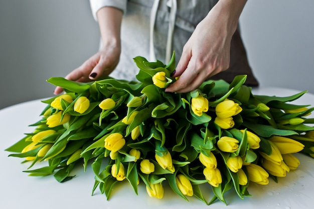Girl florist puts on the table yellow tulips.