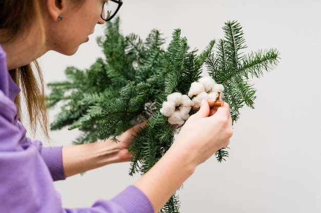 Girl florist with a hanging pine garland. woman florist decorating.