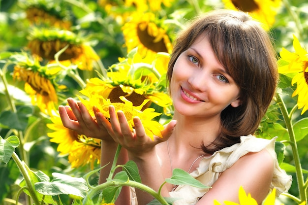 Girl in flower field with sunflower in hands