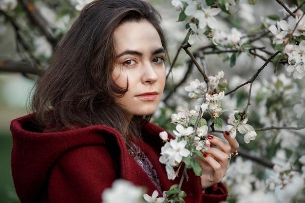 Girl in a flowery garden in a maroon coat