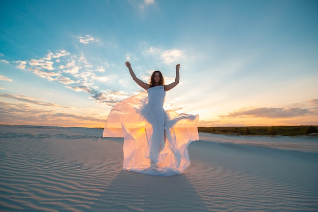 A girl in a fly white dress dances and poses in the sand desert at sunset