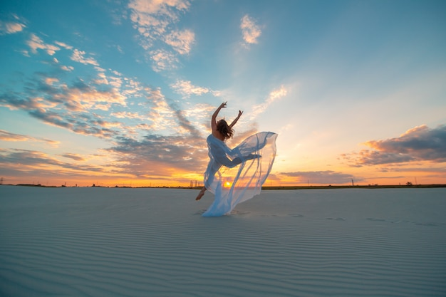 A girl in a fly white dress dances and poses in the sand desert at sunset.