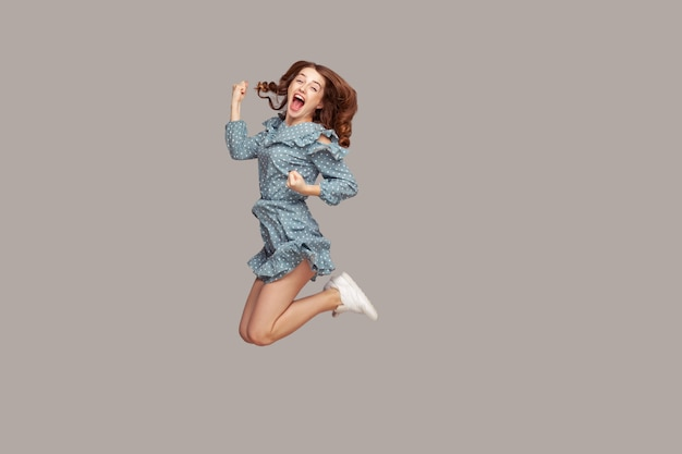Girl flying mid-air with raised fists shouting for joy, jumping trampoline looking happy