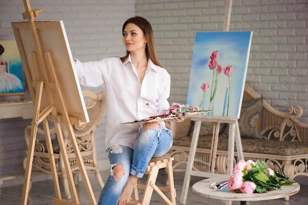 Девушка фокусируется на художественном холсте во время рисования
