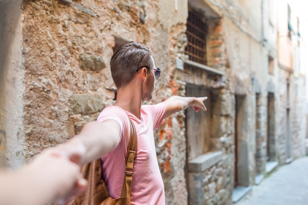 Girl following boyfriend holding hands in old european street laughing and smiling