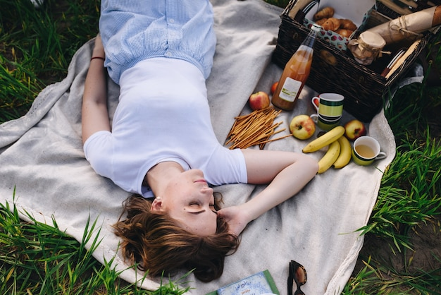 Girl in the forest at a picnic. sits on a glade, green grass. bl