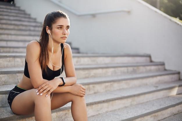 La ragazza dimentica i problemi durante il jogging, il corridore si siede all'aperto su sta