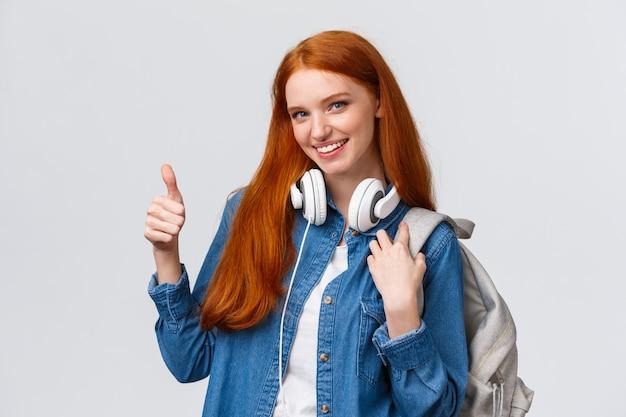 女の子は大学の授業の後、素晴らしいアルバイトを見つけました。魅力的な赤毛の女性のバックパック、首にヘッドフォン、親指のアップを示し、承認に笑みを浮かべて、推奨
