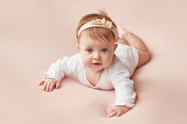 A girl of four months lies on a light pink background